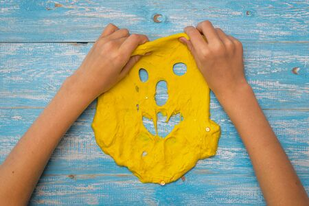 The girl stretches a face of yellow slime on a wooden table. Toy antistress. Toy for the development of hand motor skills.