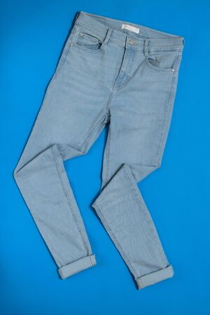 Neatly stacked on a blue background of womens jeans. Fashionable denim clothing. Flat lay. The view from the top.