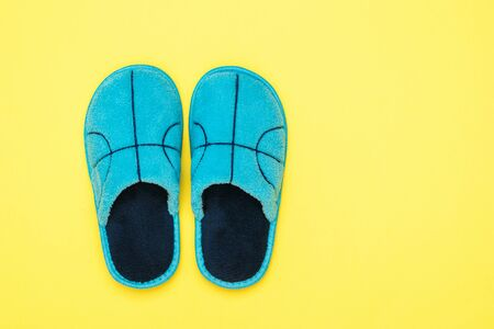 Blue Slippers on a bright yellow background. Comfortable home shoes. Flat lay.