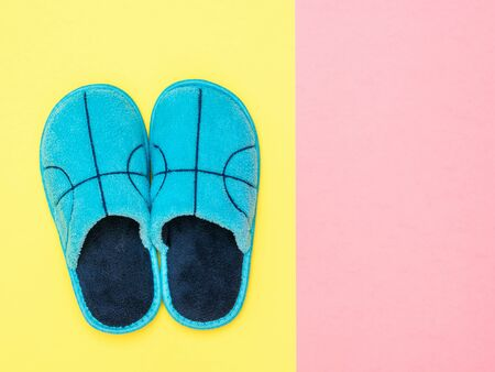 Blue Slippers on a yellow and pink background. Comfortable home shoes. Flat lay. Stock Photo