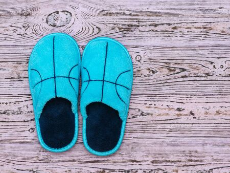 Blue Slippers on a pink wooden background. Comfortable home shoes. Flat lay.