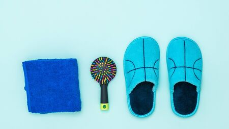 Blue Slippers, towel and comb on blue background. Set of morning accessories. Stock Photo