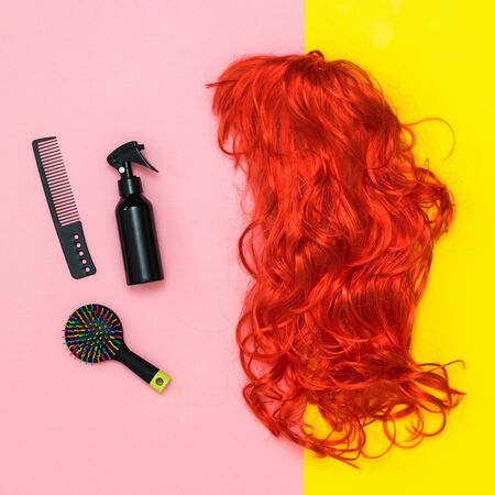 Bright wig, scissors and comb on a pink and yellow background. Lifestyle. Accessories to create style.