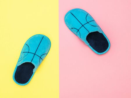 Blue house Slippers on pink and yellow background. Comfortable home shoes. Flat lay.
