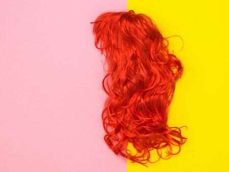 Bright orange wig on yellow and pink background. Lifestyle. Accessories to create style. Imagens