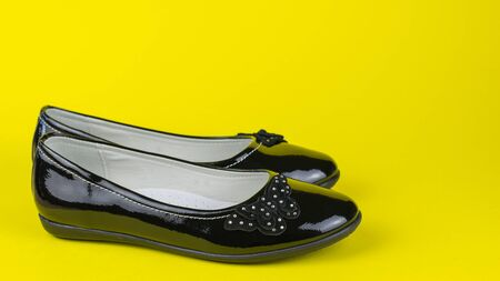 Leather leather shoes on bright yellow background. Fashionable school shoes.