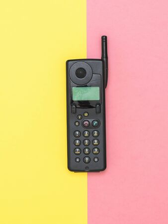 Retro mobile phone with antenna on yellow and pink background. Retro means of communication. Technology of the past. Imagens