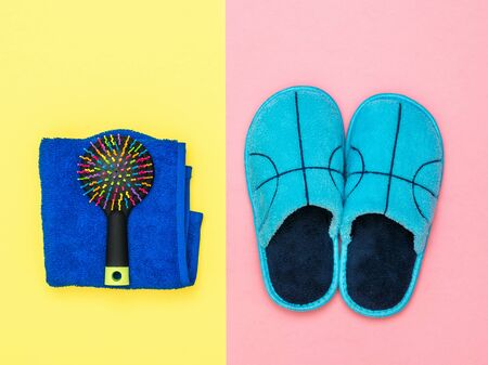 Blue Slippers and towel and comb on pink and yellow background. Set of morning accessories.