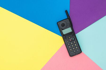 Retro mobile phone with antenna on colorful background. Retro means of communication. Technology of the past. Imagens