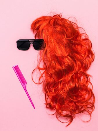 Sunglasses, orange wig and red comb on pink background. Lifestyle. Accessories to create style.