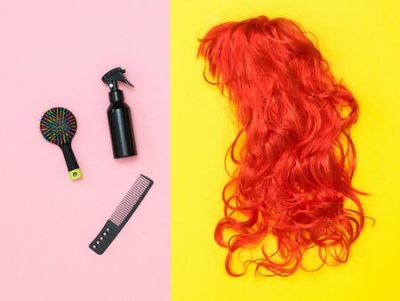Hair care products and a bright orange wig on a two-tone background. Lifestyle. Accessories to create style. Imagens - 130201146