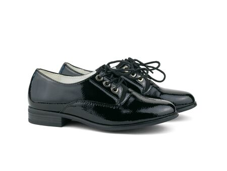 Black patent leather shoes with tied laces izolirovannye on a white background. Fashionable school shoes.