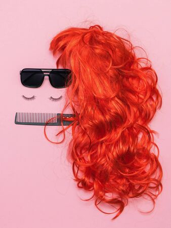 Wig with sunglasses, eyelashes and comb on pink background. Lifestyle. Accessories to create style.