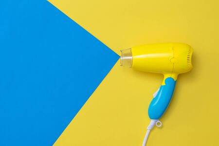 Image simulating the flow of air from a hair dryer on a yellow background. Devices for drying hair on a colorful background. Фото со стока