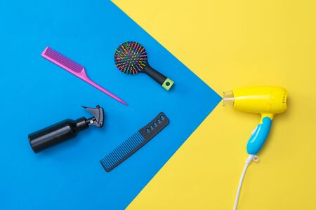 Hairdressing accessories flying out of the hair dryer. Devices for drying hair on a colorful background.
