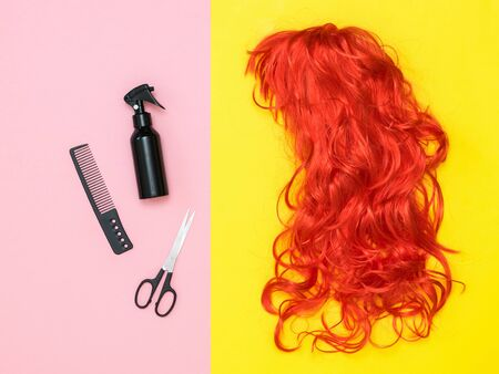Bright orange wig and hair styling accessories on a colored background. Lifestyle. Accessories to create style. Фото со стока