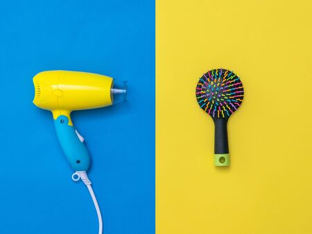 Yellow-blue hair dryer and color comb on yellow-blue background. Devices for drying hair on a colorful background.