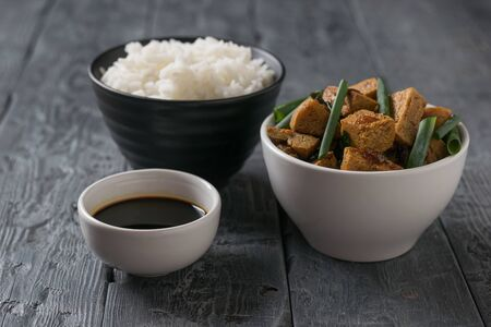 A bowl of rice and a bowl of tofu cheese on a wooden table. Vegetarian Asian dish. Banco de Imagens