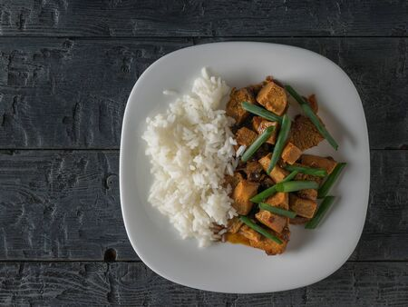 Green onions with fried tofu cheese and rice on a wooden table. Flat lay. Vegetarian Asian dish.