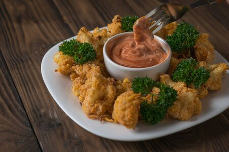 Fork with a piece of baked cauliflower and sauce on a wooden table. Vegetarian cauliflower appetizer.