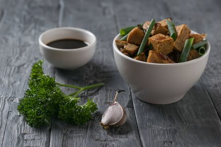 A bowl of fried tofu with herbs and soy sauce on a wooden table. Vegetarian Asian dish. Banco de Imagens