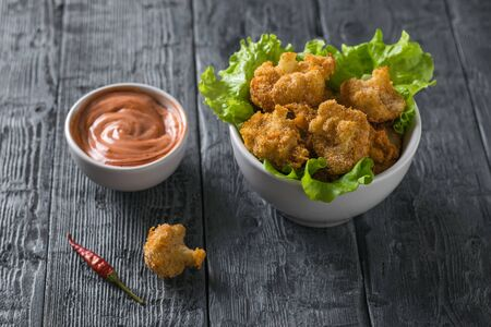 Baked cauliflower on lettuce leaves in a bowl of sauce on a wooden table. Vegetarian cauliflower appetizer. Stockfoto