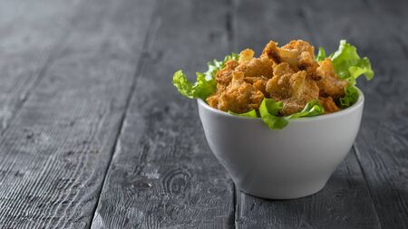 A deep white bowl with baked cauliflower and lettuce on a wooden table. Vegetarian cauliflower appetizer.