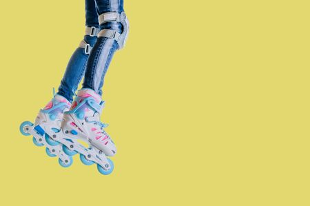 Childs legs in jeans and roller skates on a yellow background. Space for text. Leisure and sports.