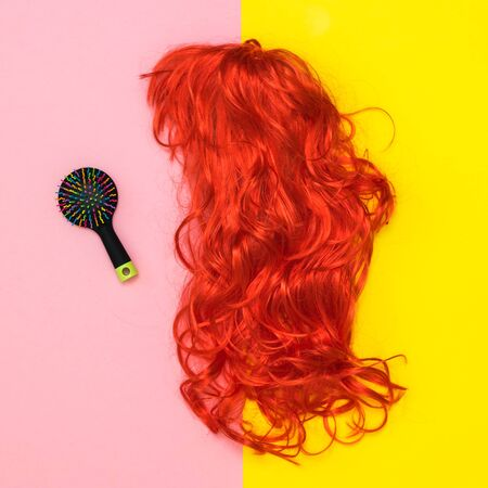 Bright wig and comb on yellow and pink background. Lifestyle. Accessories to create style. Flat lay.