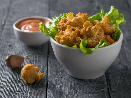 Roast florets of cauliflower in a white bowl with the sauce. Vegetarian cauliflower appetizer.