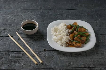 A bowl of rice and fried tofu cheese and soy sauce on the table. Vegetarian Asian dish.