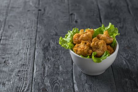 Top view of a white bowl with lettuce leaves and baked cauliflower. Vegetarian cauliflower appetizer. Stockfoto