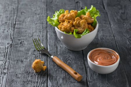A fork of sauce and a bowl of baked cauliflower. Vegetarian cauliflower appetizer. Stockfoto