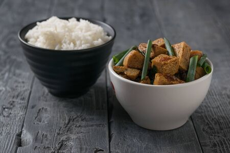 Roast tofu in a white bowl and rice in a black bowl on a wooden table. Vegetarian Asian dish. Banco de Imagens