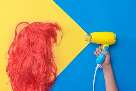 The childs hand directs the hair dryer to the bright orange wig. Hair care concept. Create a new style. 版權商用圖片