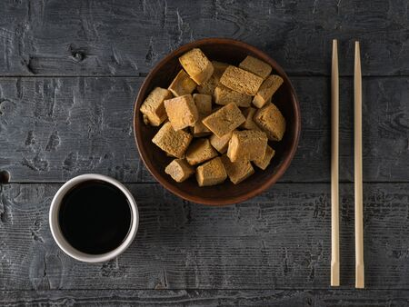 Fried tofu cheese, soy sauce in a white bowl and chopsticks on a wooden table. Grilled cheese appetizer. Flat lay. Banco de Imagens