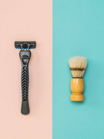 Modern men's razor and shaving brush on a two-tone background. Set for care of a man's face. Flat lay.