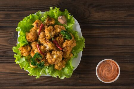 Baked cauliflower blossoms on lettuce leaves and red and white sauce. Vegetarian cauliflower appetizer.