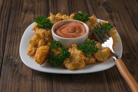 Bowl of sauce in a plate with baked cauliflower. Vegetarian cauliflower appetizer.