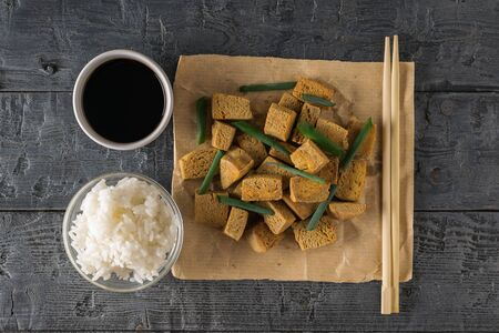 Rice, soy sauce, chopsticks and grilled tofu cheese on a wooden table. Grilled cheese appetizer. Flat lay.