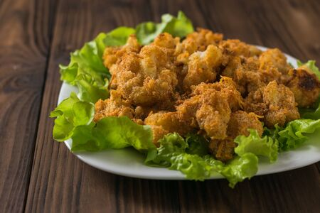 Baked cauliflower on lettuce leaves on a white plate. Vegetarian cauliflower appetizer. The view from the top. Stockfoto