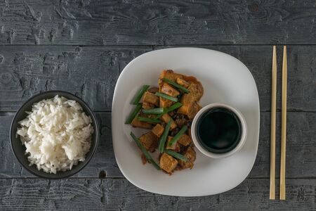 Roast tofu with rice and soy sauce on a white plate. Flat lay. Vegetarian Asian dish.