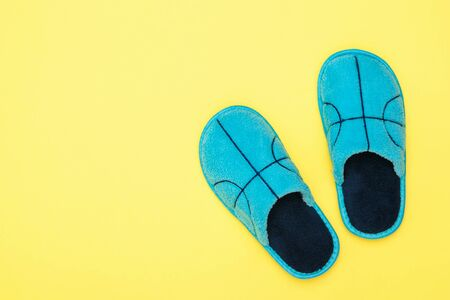 Top view of blue Slippers on yellow background. Comfortable home shoes. Flat lay. Stock Photo