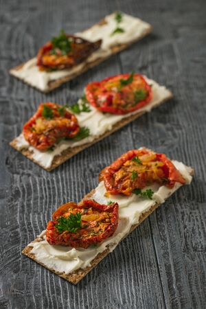 Three toasted breads with cream cheese and sun-dried tomatoes on a wooden table. Vegetarian snack of cottage cheese and tomatoes.