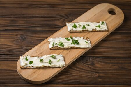 Cutting Board with three toasts with cream cheese and herbs on a wooden table. Vegetarian snack. Vegetables with cream cheese and bread. Banque d'images - 132096252