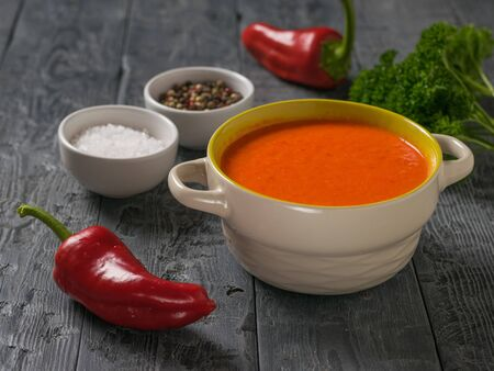 Two bell peppers with cream soup and seasonings on a wooden table. Soup of the vegetarian diet.