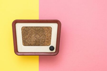 Retro radio in brown case on pink and yellow background. Radio engineering of the past time. Retro design. The view from the top.