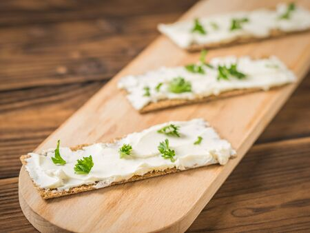 Bread toast with cream cheese and parsley on a cutting Board. Vegetarian snack. Vegetables with cream cheese and bread. Stock Photo