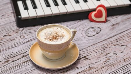 A red heart on the keys and a Cup of cinnamon coffee on the wooden table. Break in work on processing music.