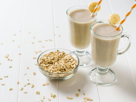 Banana smoothie and oatmeal scattered on a white wooden table. Vegetarian smoothie. Sports nutrition. 版權商用圖片